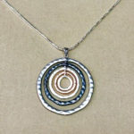 18-inch silver coloured costume necklace with circular drop in silver, rose gold and pewter