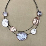 Black double strand costume necklace with pewter, silver and rose gold discs