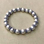 Costume elasticated bracelet in a matt hammered silver colour with pale grey discs