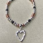 Costume elasticated bracelet in a rose gold, grey and silver colour with an open hammered heart charm