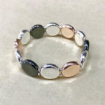 Costume elasticated bracelet in a shiny rose gold, silver and black colour