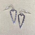 Elongated heart shape silver coloured earrings with a hammered finish