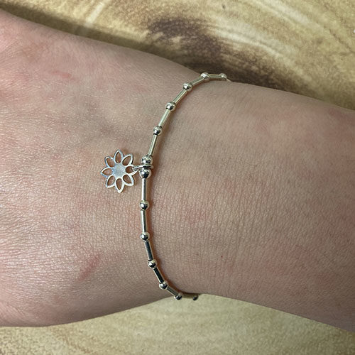 Silver tube and bead bracelet with flower charm