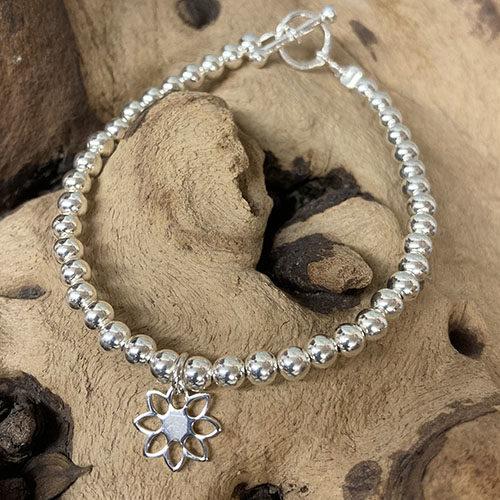Sterling silver bracelet with open flower charm