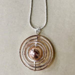 Long 34-inch silver coloured costume necklace with silver and rose gold circular pendant