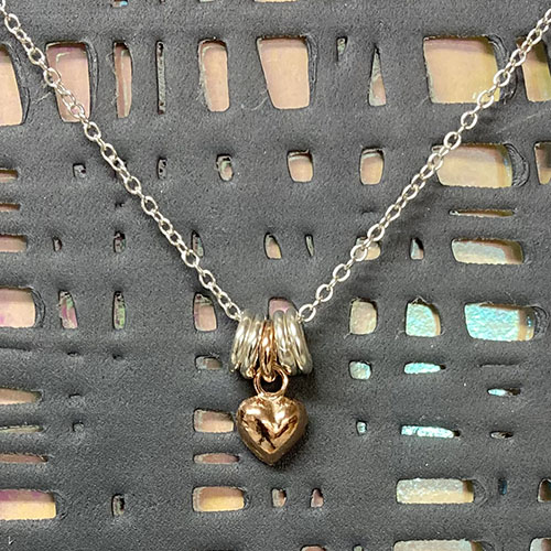 silver and rose gold pendant with small heart