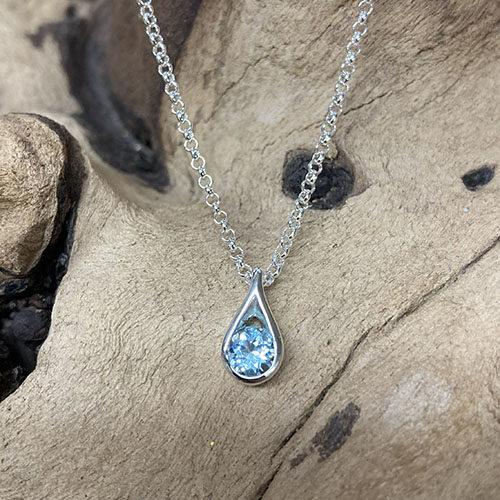 Silver teardrop pendant with blue topaz